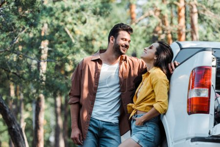 happy bearded man standing and looking at girl smiling near car
