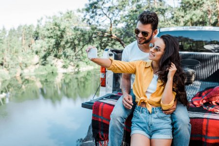 Photo for Cheerful girl in sunglasses talking selfie with man near car and lake - Royalty Free Image