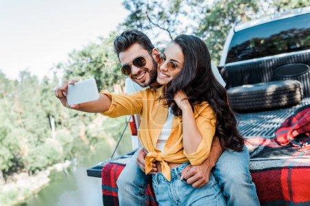 Photo pour Fille gaie dans des lunettes de soleil parlant le selfie avec l'homme barbu près de la voiture - image libre de droit