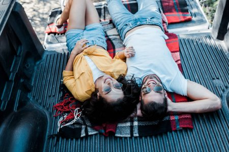 overhead view of woman in sunglasses lying with handsome man in plaid blanket in car trunk