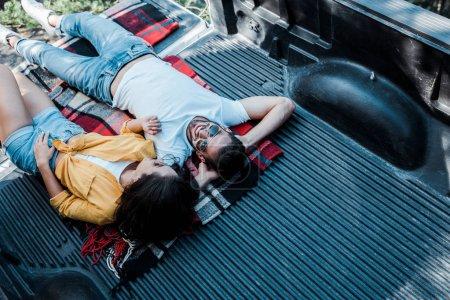 vue aérienne de la femme dans les lunettes de soleil couché avec l'homme heureux dans la couverture à carreaux dans le coffre de la voiture