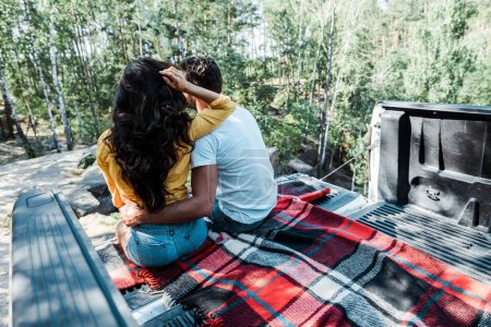 back view of man hugging woman while sitting in car trunk in woods
