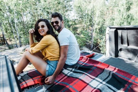 Photo for Selective focus of man hugging woman while sitting in car trunk in woods - Royalty Free Image