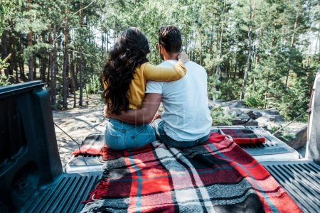 Photo for Back view of young woman and man hugging while sitting in car trunk in woods - Royalty Free Image