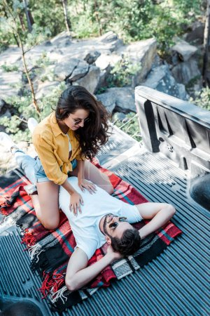 cheerful girl in sunglasses looking at handsome man lying on blanket