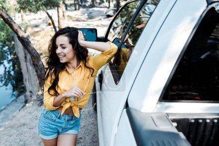 Photo pour Foyer sélectif de sourire heureux de femme tout en restant près de la voiture dans les bois - image libre de droit