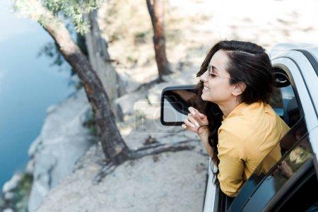 Photo pour Fille heureuse dans des lunettes de soleil souriant de la fenêtre de voiture dans les bois - image libre de droit