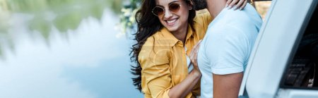 Photo for Panoramic shot of girl hugging with boyfriend near automobile and river - Royalty Free Image