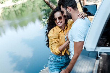 Photo for Selective focus of happy girl hugging with boyfriend near car and river - Royalty Free Image