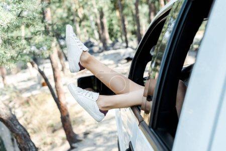 Photo pour Mise au point sélective des baskets blanches de la jeune femme dans les bois - image libre de droit
