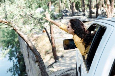Photo pour Fille gaie agitant la main de la fenêtre de voiture dans les bois - image libre de droit
