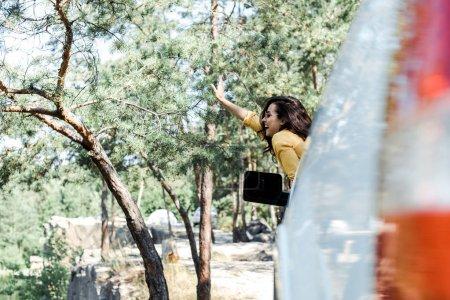 Photo pour Foyer sélectif de la fille gaie agitant la main de la fenêtre de voiture dans les bois - image libre de droit
