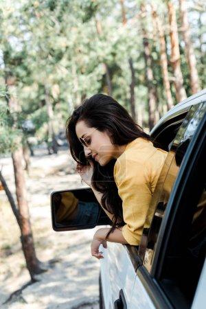 Photo pour Foyer sélectif de gaie fille souriant de la fenêtre de la voiture dans les bois - image libre de droit