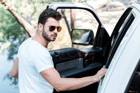 Photo pour Foyer sélectif de l'homme barbu dans des lunettes de soleil restant près de la voiture - image libre de droit