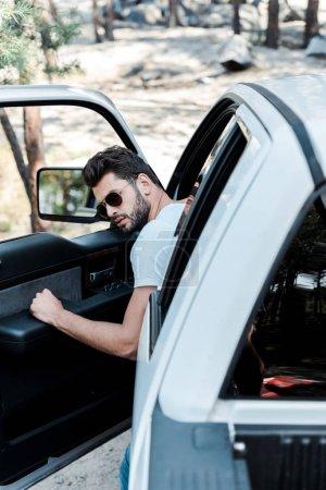 Photo pour Foyer sélectif de l'homme dans la porte d'ouverture de voiture de lunettes de soleil - image libre de droit