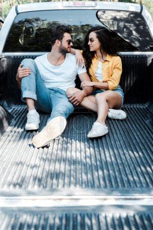 Photo pour Homme gai dans des lunettes de soleil assis dans le coffre de la voiture et regardant fille - image libre de droit