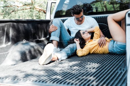 Photo pour Homme barbu dans des lunettes de soleil assis dans le coffre de la voiture et regardant fille - image libre de droit