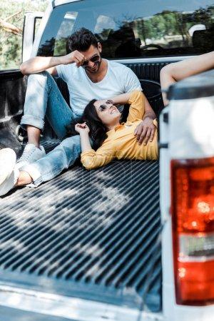 Photo pour Foyer sélectif de l'homme barbu dans les lunettes de soleil assis dans le coffre de la voiture et en regardant la fille - image libre de droit