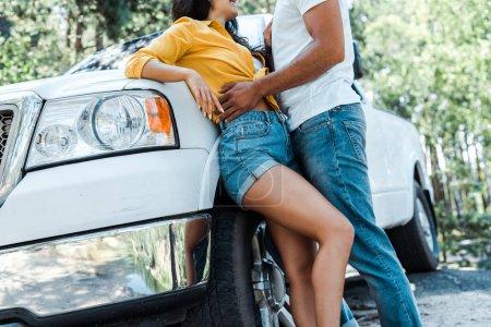 Photo pour Vue recadrée de l'homme restant avec la femme près de l'automobile dans les bois - image libre de droit