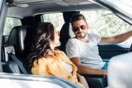 Photo for Selective focus of handsome man looking at girl in car - Royalty Free Image