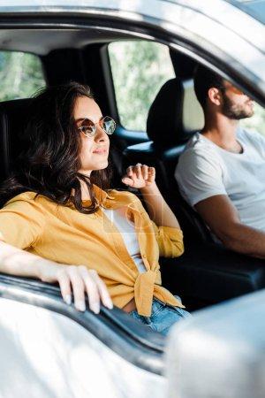 Photo pour Foyer sélectif de la fille attirante près du conducteur dans la voiture - image libre de droit