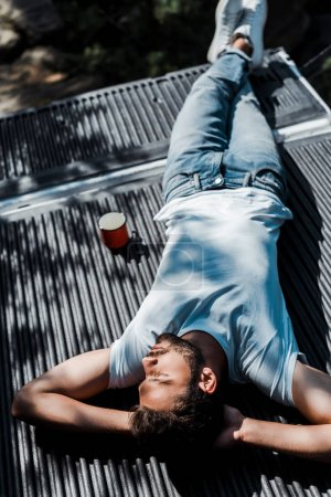 Photo for Overhead view of bearded man lying with closed eyes near cup - Royalty Free Image