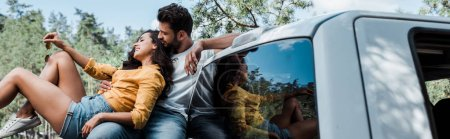 Photo for Panoramic shot of bearded man sitting and looking at happy girl in woods - Royalty Free Image