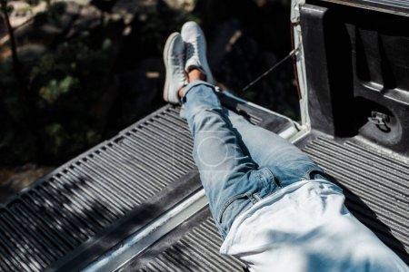 overhead view of man lying in blue denim jeans in car trunk