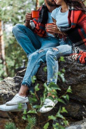 Photo pour Vue recadrée de l'homme et de la femme s'asseyant près des arbres et retenant des tasses avec le thé - image libre de droit