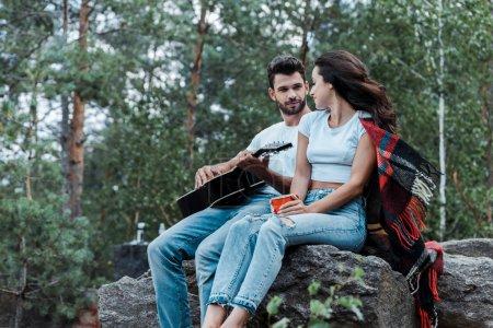 Photo pour Foyer sélectif de l'homme retenant la guitare acoustique et regardant la fille - image libre de droit