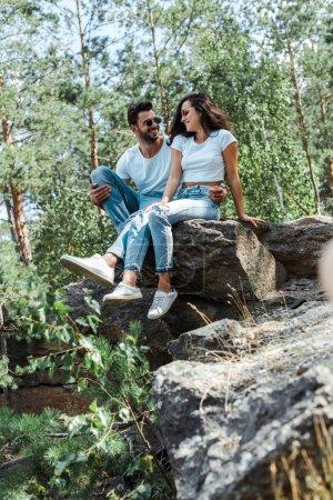 Photo pour Foyer sélectif de l'homme et de la femme s'asseyant sur des roches près des arbres - image libre de droit