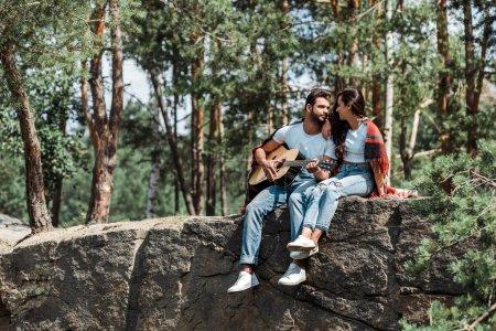 Photo pour Homme barbu jouant la guitare acoustique près de la femme dans les bois - image libre de droit