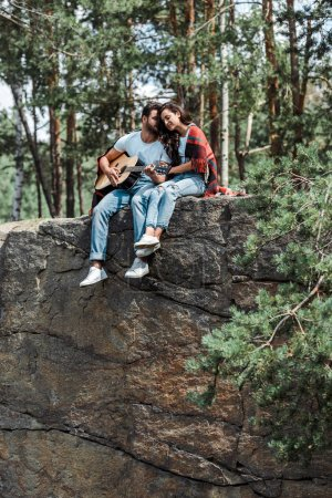 Photo for Bearded man playing acoustic guitar near attractive woman in woods - Royalty Free Image