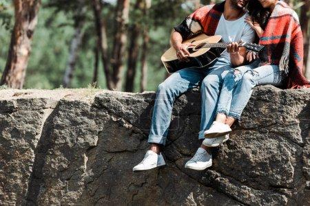 Photo pour Vue recadrée de l'homme jouant la guitare acoustique près de la jeune femme enveloppée dans la couverture - image libre de droit