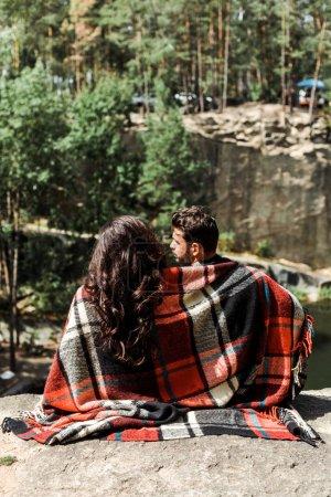 Photo pour Vue arrière de la fille et de l'homme enveloppés dans la couverture de plaid dans les bois - image libre de droit