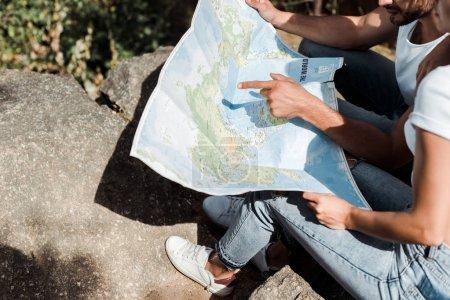 Photo pour Vue recadrée de l'homme pointant avec le doigt à la carte près de la fille - image libre de droit