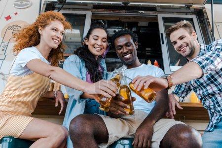 Photo pour Amis multiculturels heureux clignotant des bouteilles avec la bière près du camion de nourriture - image libre de droit