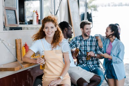 Photo for Selective focus of happy redhead girl holding bottle with beer near friends and food truck - Royalty Free Image