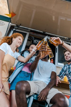 Photo for Low angle view of happy multicultural friends clinking bottles with beer near food truck - Royalty Free Image