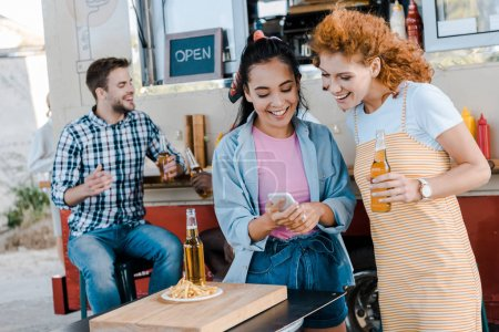 Photo for Selective focus of happy girls looking at smartphone near multicultural men and food truck - Royalty Free Image