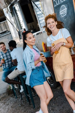 Photo for Selective focus of happy women holding bottles with beer near multicultural men and food truck - Royalty Free Image