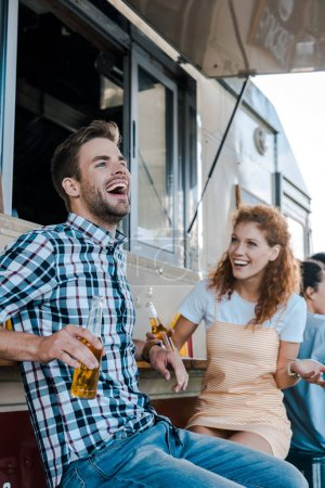 Photo for Selective focus of happy man laughing near redhead girl near food truck - Royalty Free Image