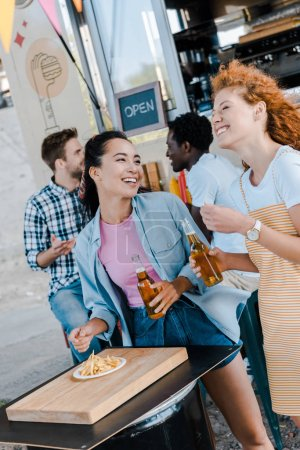 Photo for Selective focus of happy girls smiling near multicultural men and food truck - Royalty Free Image