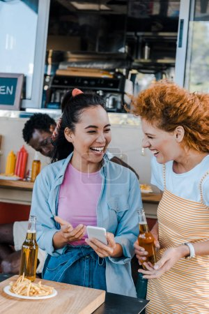 Photo for Selective focus of multicultural girls laughing near african american man and food truck - Royalty Free Image
