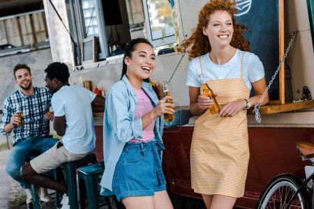 Photo for Selective focus of happy girls holding bottles with beer near multicultural men and food truck - Royalty Free Image