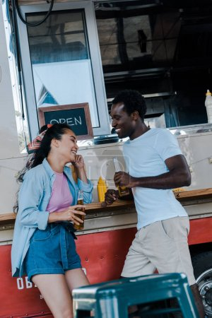 Photo for Cheerful asian girl smiling near african american man with bottle of beer - Royalty Free Image