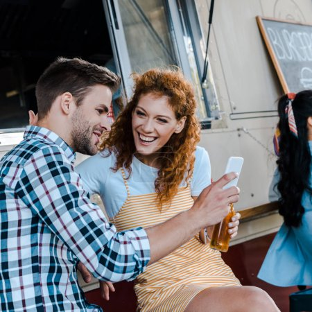 Photo for Selective focus of redhead woman looking at man holding smartphone near food truck - Royalty Free Image