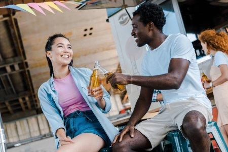Photo pour Foyer sélectif de la fille asiatique gaie souriant près de l'homme américain africain tout en clinking des bouteilles avec la bière - image libre de droit