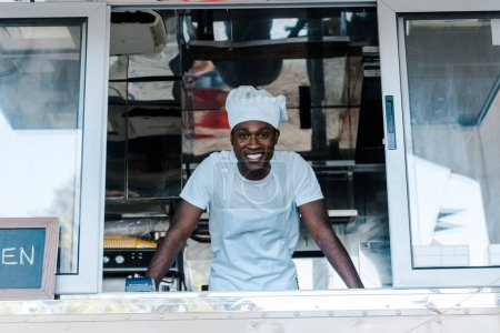 Photo for Cheerful african american man in chef uniform and hat smiling from food truck - Royalty Free Image