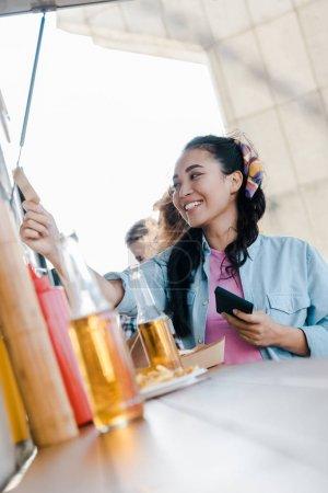 Photo pour Foyer sélectif de la femme asiatique gaie retenant la carte de crédit près des clients et du camion de nourriture - image libre de droit